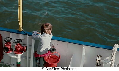 A little girl with long brown hair in a pony tail is standing closely to the board of a ship deck and looking at the water while the wind is fluttering her hair.
