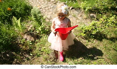 A little girl is walking in the garden with a red watering...