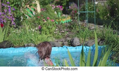 A little girl jumps into a small pond, splashing water from the jump. The child enjoys cool water on a hot summer day. Happy childhood. Flowers and grass grow around the pond