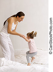 A little girl jumps on the bed with her mom
