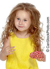 A little girl licks a candy on a stick.