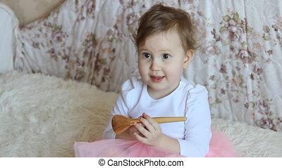 A little girl makes herself a makeup