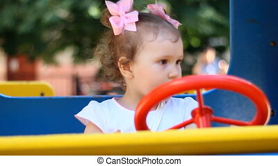 A little girl on a playground rides a car ride