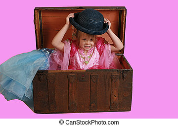 A little girl playing dress up in grandmas antique trunk.