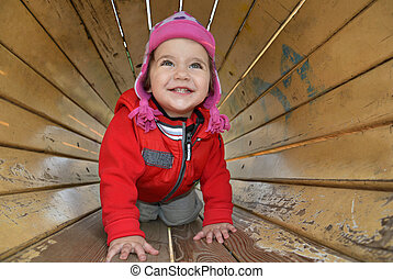 A little girl playing on the playground and laughs.
