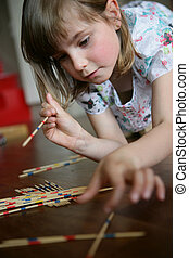 A little girl playing pick-up sticks