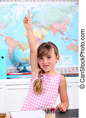 a little girl putting one's hand up in a classroom