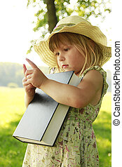 little girl reading the Bible in nature