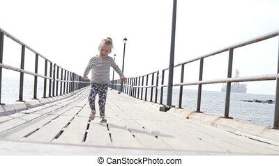 A little girl runs across the bridge