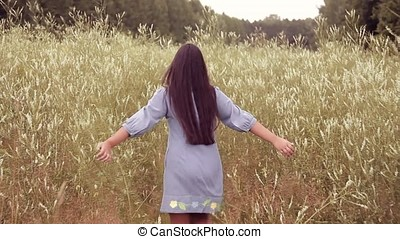 A little girl runs across the field in the forest on a sunny day. Slow motion