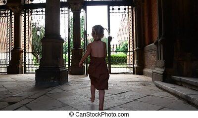 A little girl runs through the arch of an old castle