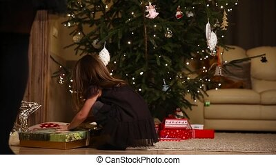 A little girl runs to open a Christmas present under the tree.
