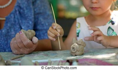 A little girl sculpts clay figurines with the help of her grandmother