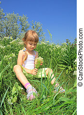 little girl sits in the grass