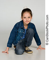 A little girl sits on the gray background