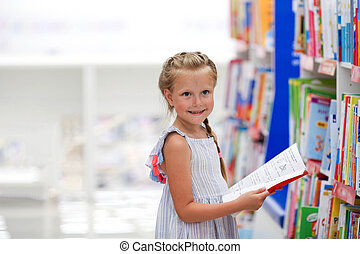 A little girl stands in a bookstore and reads.