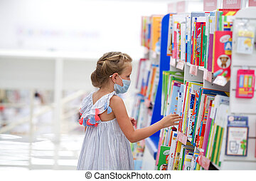 A little girl stands in a bookstore in a medical mask and reads.