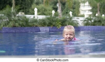 A little girl swims in the pool outside