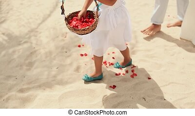 A little girl throws petals of red roses at the feet of the newlyweds. Wedding on the tropical coast. Philippines.