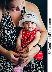 A little girl to dress sitting on mum's lap