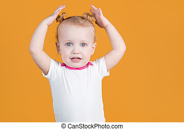 A little girl touches with her hands her cute ponytails on her head