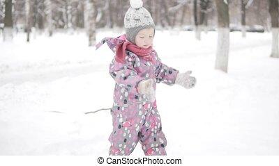 A little girl walks in a snowy park