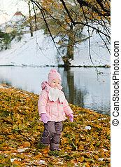 A little girl walks in autumn Park