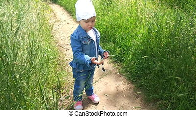 A little girl walks with her mother in the field