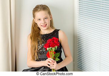 A little girl with a bouquet of flowers sits on a window sill.