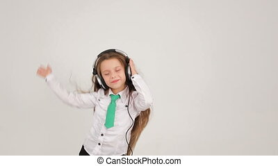 A little girl with her headphones waving her hand