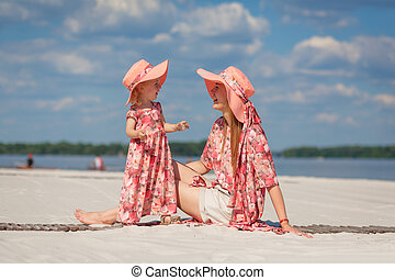 A little girl with her mother in matching beautiful sundresses plays in the sand on the beach. Stylish family look