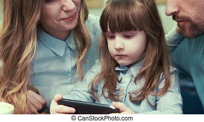 A little girl with her parents in a cafe, looking at the smartphone.