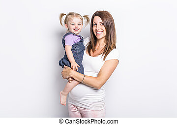 little girl with her pregnant mother in studio