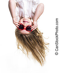 A Little girl with love glasses upside down