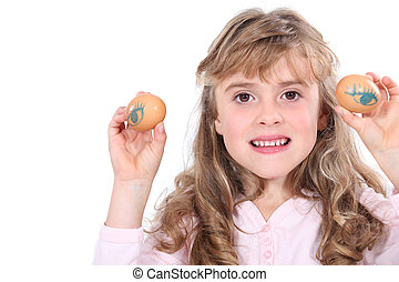 A little girl with two eggs.