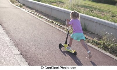 A little girl with two tails is riding a scooter in a park