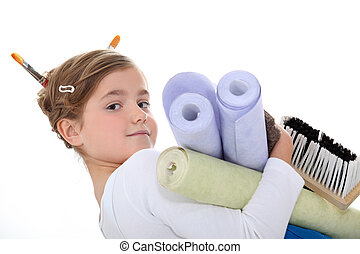 A little girl with wallpaper rolls.