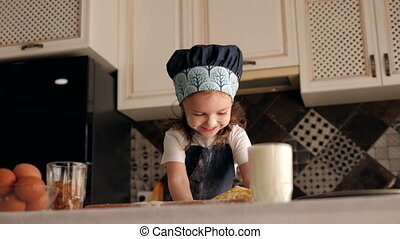 A little happy three-year-old girl is playing with dough at home in the kitchen.