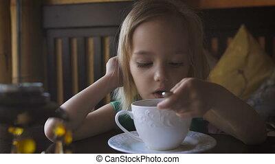 Calm morning. A little girl having breakfast at a cozy cafe. A pretty little girl drinking tea and enjoying her breakfast. A beatiful blondie having her breakfast