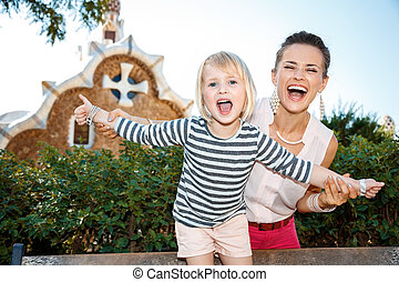 Smiling mother and child having fun time in Park Guell - A ...