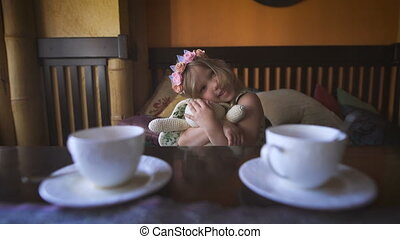 A little pretty girl is sitting on the sofa at a cafe and hugging her stuffed rabbit.