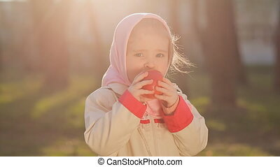 A little Russian girl in a pink headscarf eat red apple at...