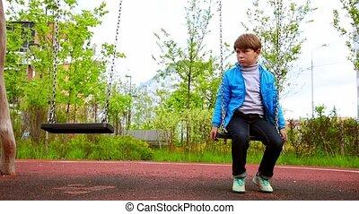 A little sad boy sitting on the swings