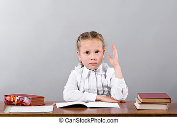A little schoolgirl sitting by the desk raising her arm signaling that she know and is ready to answer