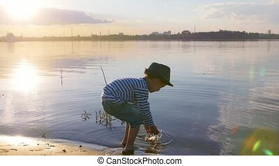 A little smiling boy in panama hat walking in the water. Mid...