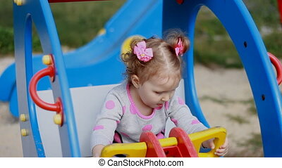 A little sweet girl is riding a carousel helicopter in an amusement park. A child plays in the playground. Entertainment for children