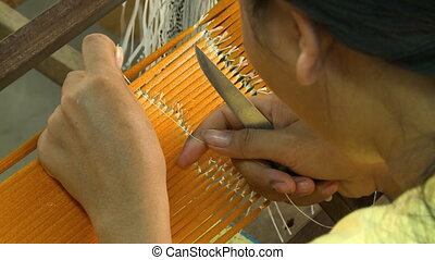 A local worker tying silk threads using a knife - An extreme...