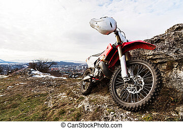A lone bike, the Eneduro motorcycle stands next to the rock against the backdrop of the city of Pyatigorsk in the Caucasus in sunny weather.