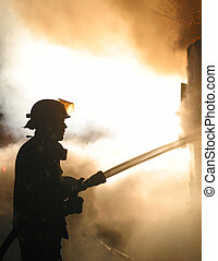 firefighter - A lone firefighter in silhouette battles a...