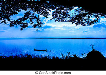 A lone fisherman moves out on a lake in a small boat as in the night blue tone